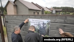 Актывісты вывешваюць плякаты на агароджы забаўляльнага комплексу, у якім адкрылася рэстарацыя, 7 чэрвеня 2018