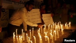 Members of Pakistan's Shi'ite community light candles for the victims and to condemn the attack on a bus in Karachi on May 13.