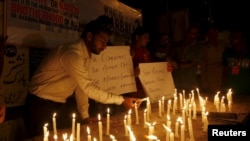 Members of the Shi'ite community light candles for the victims and to condemn the attack on a bus, in Karachi, Pakistan on May 13.