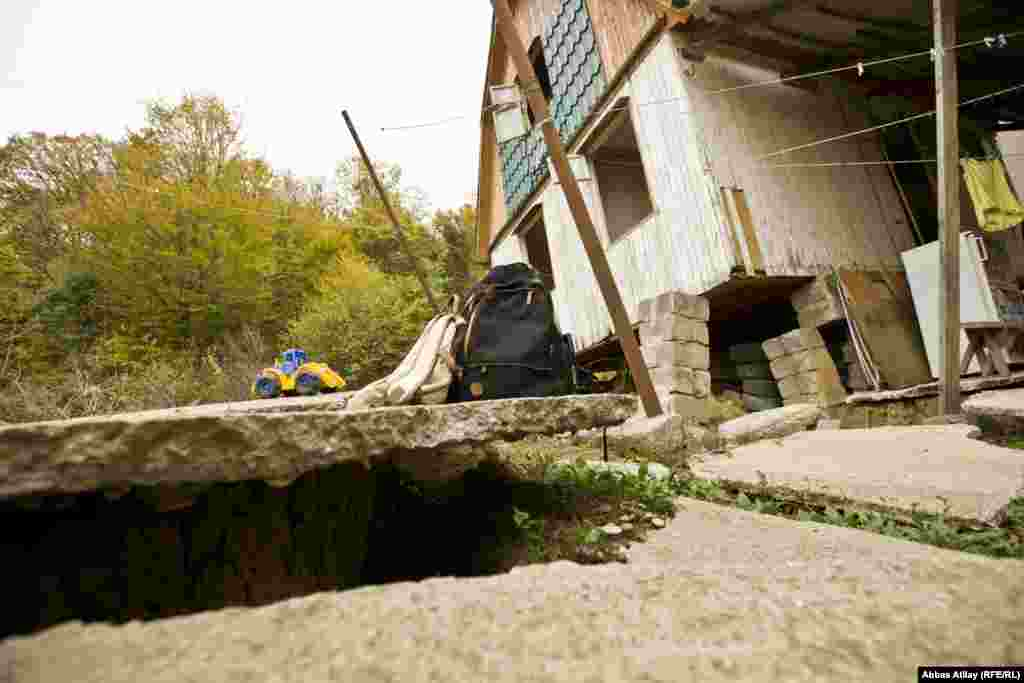 The old house where Dmitry Abzhan grew up is now propped up on concrete blocks. The family moved into a new house that was under construction when the landslide struck. Abzhan is scared to allow his young children to play outside out of fear that this building could collapse.