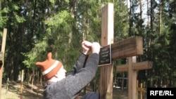 Ільля Копыль прымацоўвае шыльдачку на крыжы па сваім дзядзьку ў Курапацкім лесе