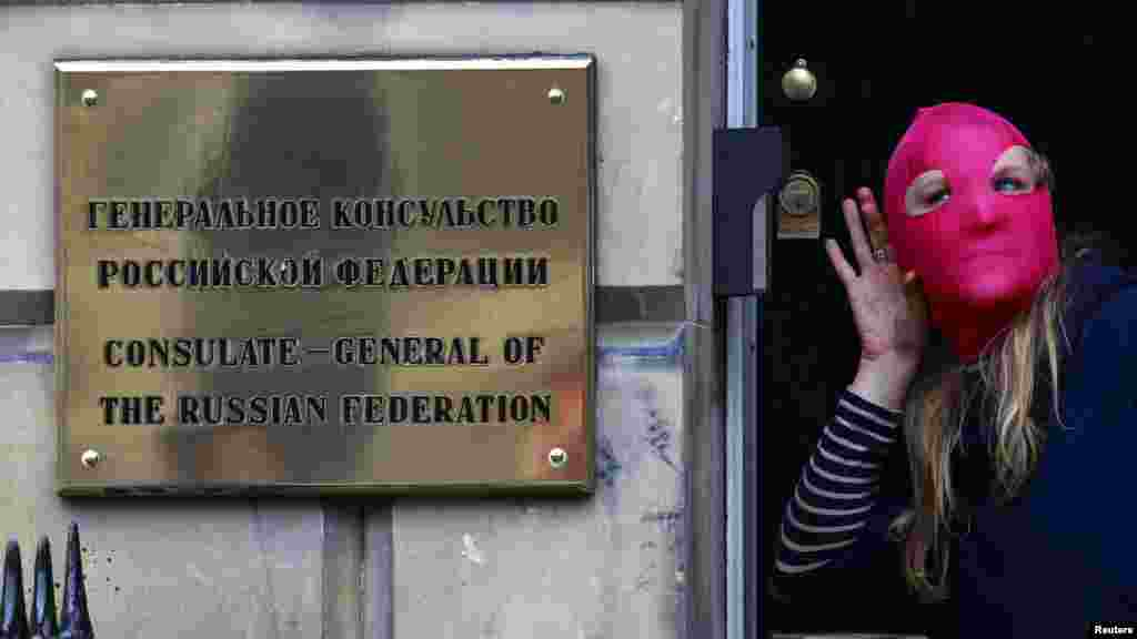 A protester gestures next to a sign outside the Russian Consulate building during a demonstration of support for Pussy Riot in Edinburgh, Scotland, on August 17.