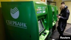 Russia -- People use an automated teller machine inside a branch of Sberbank in St. Petersburg, November 5, 2014
