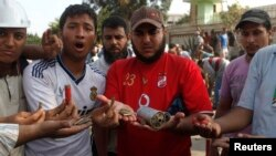 Египет -- Бийликтен кулатылган президент Мурсинин тарапкерлери атылган ок-дарылардын калдыктарын кармап турат. Каир, 8-июль, 2013.