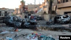 Residents walk through the site of a car bomb attack in eastern Baghdad.