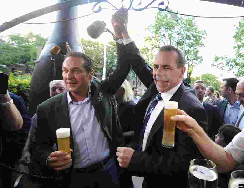 The head of the far-right Freedom Party of Austria, Heinz-Christian Strache (left), and fellow candidate Harald Vilimsky celebrate the preliminary results, which showed their party with some 20 percent of Austria's vote.