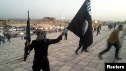Вооруженный человек с флагом экстремистской группировки «Исламское государство». Иллюстративное фото.