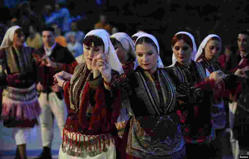 Women dance in traditional folk costumes.