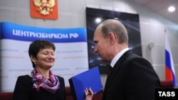 Russian Prime Minister Vladimir Putin (right) presents documentation for his candidacy in the 2012 presidential election, to a Central Electoral Commission official in Moscow on December 7.