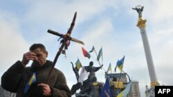 A pro-EU protester crosses himself during a religious service on Independence Square in Kyiv on December 13.