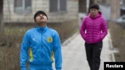 Тяжелоатлетки Зульфия Чиншанло (слева) и Светлана Подобедова идут в тренировочный зал для подготовки в Олимпийским играм. Алматы, 29 марта 2012 года.