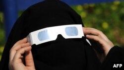 Күннің тұтылуын көзәйнектен қызықтап қарап тұрған сауд арабиялық әйел. Джидда, 15 қаңтар 2010 жыл