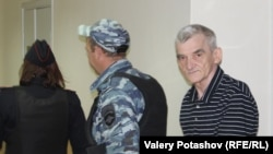 Yury Dmitriyev is escorted to court in Petrozavodsk.