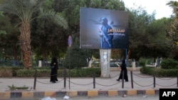 Women wearing a niqab, a type of full veil, walk under a billboard erected by the Islamic State (IS) group as part of a campaign in the IS-controlled Syrian city of Raqqa on November 2.