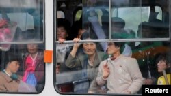 North Koreans look out of a tram as it passes by a department store in central Pyongyang. While some basic shopping is permitted, most North Koreans lived in poverty and rely on the state ration system for survival.