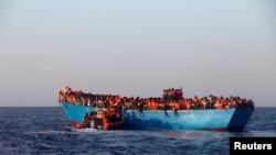 Испанские спасатели подплывают к переполненной лодке с мигрантами (у берегов Ливии, август 2016 г.)
