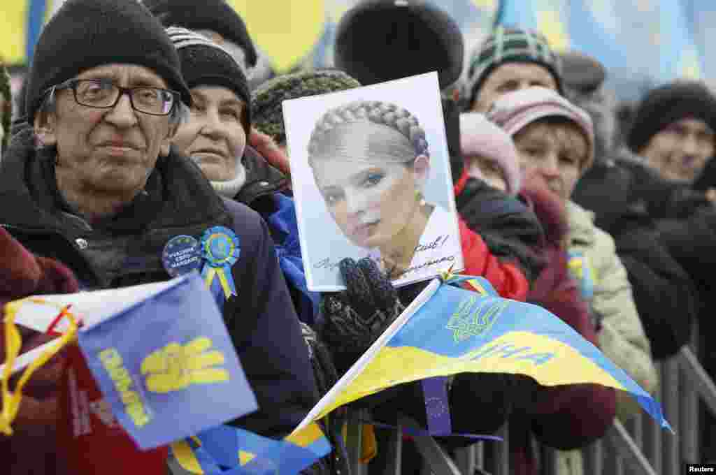 A pro-EU protester holds a portrait of jailed opposition leader Yulia Tymoshenko.