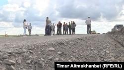 Құрылысы тоқтап тұрған Орталық - Шығыс автожолында тұрған жұмысшылар. Павлодар облысы, 26 шілде 2016 жыл.