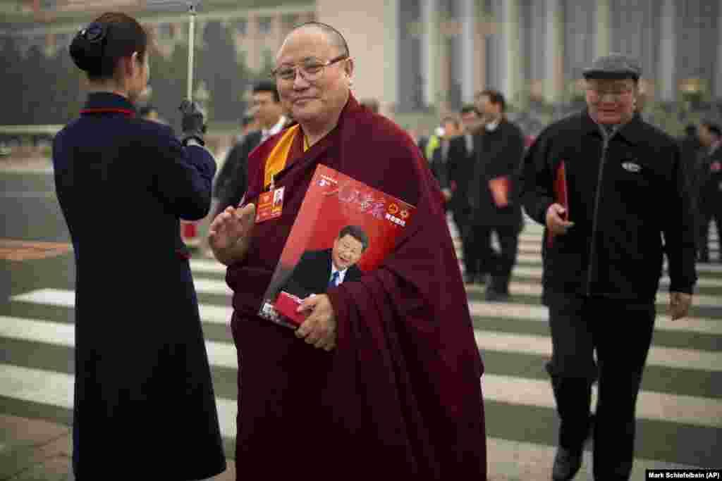 Си Цзиньпиннің суреті басылған журнал ұстап тұрған монах.