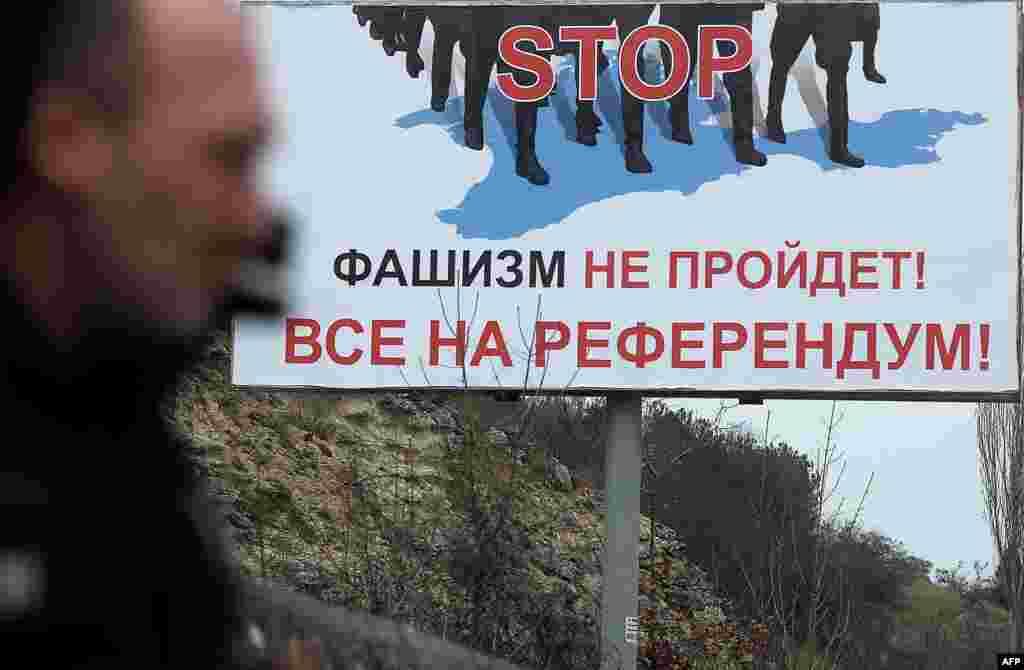 """Билборды на улицах Крыма перед """"референдумом"""", назначенным на 16 марта, его дата была перенесена с более позднего срока на ранний. Еще до того, как голосование состоялось, 11 марта в Госдуму были внесены законопроекты, предусматривающие ускоренную процедуру аннексии территории другого государства. Если ранее, согласно российским законам, это было возможным только при заключении двухстороннего международного договора с Украиной, то принятые впоследствии законодательные нормы позволяли делать это в одностороннем порядке."""