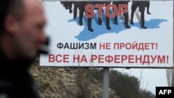"A man walks passed a billboard reading ""STOP, fascists won't pass, let's all go to the referendum"" on the main road entering the Crimean city of Sevastopol."