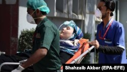 A person is rushed to a hospital for medical treatment in Karachi on February 19.