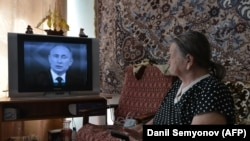 An elderly woman watches a TV broadcast of Russian President Vladimir Putin's annual televised question-and-answer session in 2014. (file photo)
