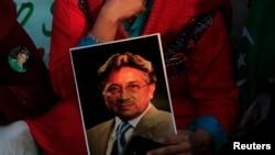 Një mbështetës e mbanë fotografinë e Pervez Musharrafit gjatë një proteste për proces korrekt kundër tij