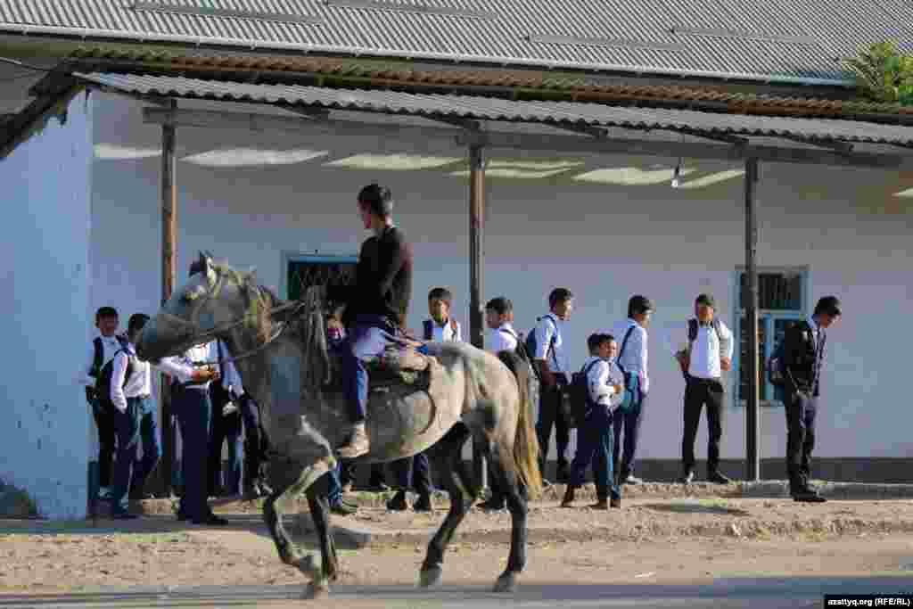 Автобус күтіп тұрған мектеп оқушылары мен ат мінген ауыл тұрғыны.
