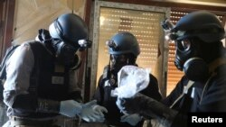 A UN chemical weapons expert, wearing a gas mask, holds a plastic bag containing samples from one of the sites of an alleged chemical weapons attack in the Ain Tarma neighbourhood of Damascus last August.