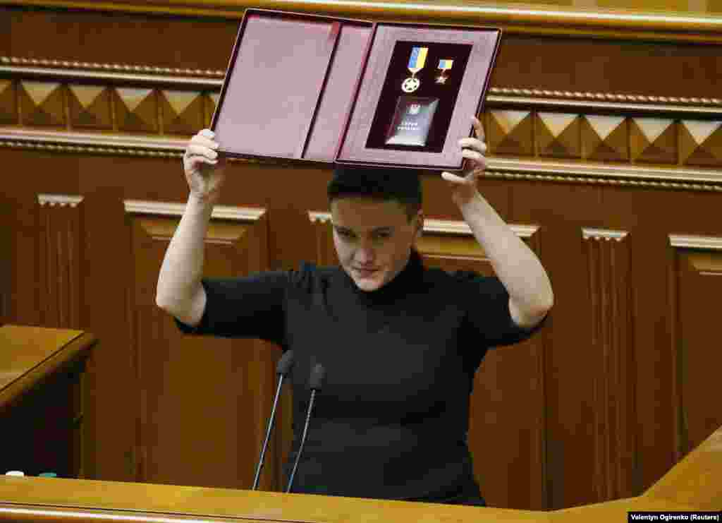 "22-nji martda ukrain parlamentiniň deputaty Nadia Sawçenko özüniň Ukrainanyň gahryman ýyldyzy baradaky sylagyny görkezýär. Şondan gysga wagt soň, Sawçenko tussag edildi. Sawçenko kanun çykaryjy organa ""terrorçylykly"" hüjümiň dildüwşügni etmekde aýyplanýar.(Reuters/Valentyn Ogirenko)"