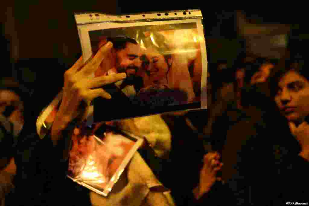 A woman holds a picture of newlywedsArash Pourzarabi and Pouneh Gourji at a Tehran vigil on January 11. Both were graduate students studying computer science at the University of Alberta, and were coming back to Edmonton, Canada after celebrating their wedding in Iran.