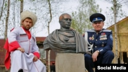 Cossacks pose next to a bust of Vladimir Putin in the guise of a ROman emperor.