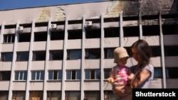 Мама з дитиною біля будівлі в Маріуполі, пошкодженого внаслідок обстрілу реактивними системами залпового вогню