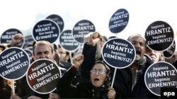 "People hold signs reading :We are all Armenian, we are all Hrant"" during a rally to mark the eighth anniversary of his murder in front of the Agos newspaper in Istanbul on January 19."