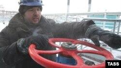 A worker adjusts a valve at a Gazprom gas field.