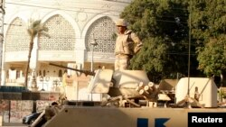Esger prezident köşgüniň öňünde, harby maşynyň üstünde dur. Kair, 14-nji iýul, 2013 ý.