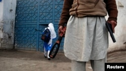 A man with a gun and a metal detector poses for photographers while he stands outside a school in Peshawar.