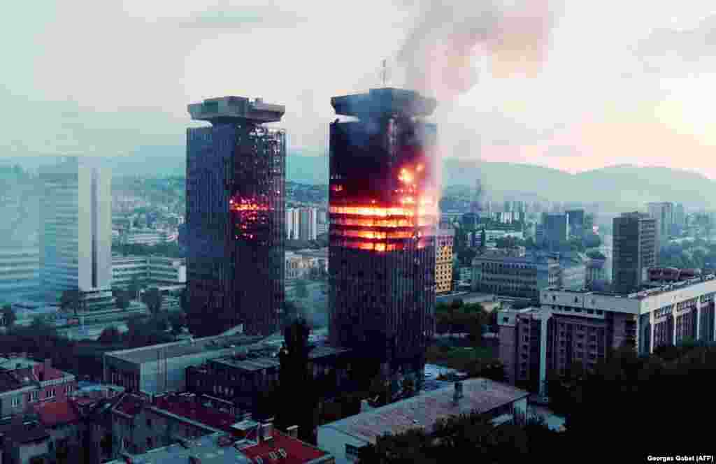 A tower burns in downtown Sarajevo on June 8, 1992, as paramilitary groups in the surrounding hills fire mortars and artillery down on the blockaded city.
