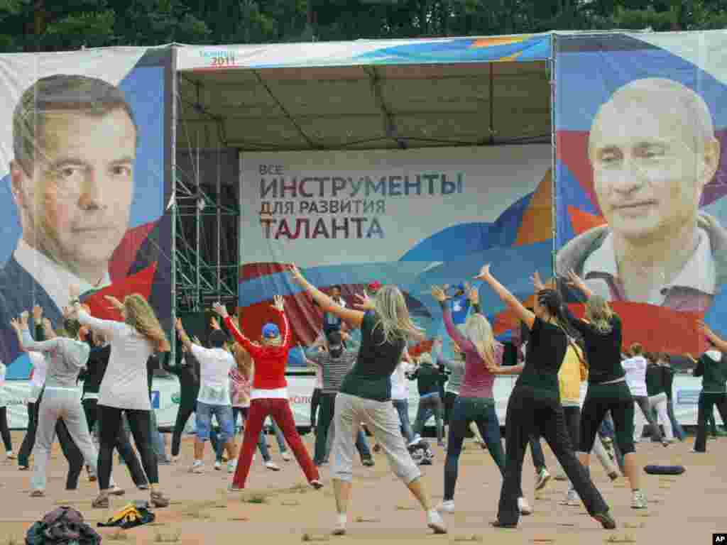 Pro-Kremlin youth activists dance in front of portraits of Russian President Dmitry Medvedev (left) and Prime MInister Vladimir Putin at a summer camp near Lake Seliger. Thousands of pro-Kremlin youth activists visit the Seliger forum annually. The Russian opposition accuses the groups of staging attacks and pranks on government critics.Photo by Mikhail Metzel for AP