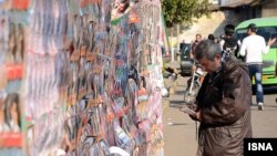 An Iranian man looks at election posters during a week of campaigning ahead of a parliamentary poll on March 2