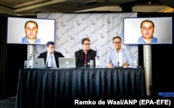 Bellingcat founder Eliot Higgins (center) presents a picture of Russian military officer Oleg Ivannikov at a press conference on May 25.