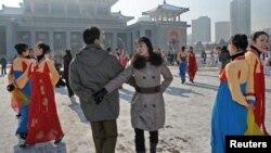 """Түндүк кореялыктар """"Ынхи-3"""" ракетасынын ийгиликтүү сыналганын майрамдап, Пхеняндын борбордук аянтында бийлешүүдө. 12-декабрь 2012"""