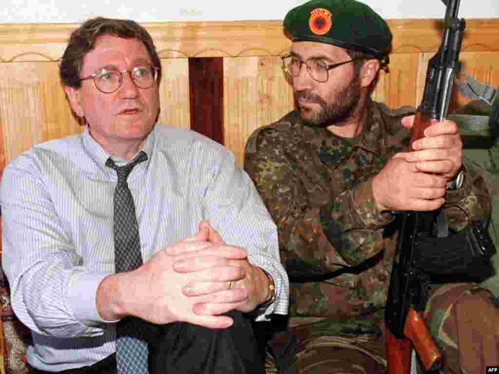 Richard Holbrooke sits with an unidentified member of the Kosovo Liberation Army at KLA headquarters in Junik, southwest of Pristina, during a shuttle diplomatic effort to stop violence in Kosovo on June 24, 1998.