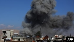 Дим піднімається від будівель після авіаудару урядових військ на місто Дума, 23 грудня 2014 року