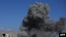 Дым над зданиями в городе Дума после авиаударов, нанесенных правительственными войсками, 23 декабря 2014 года