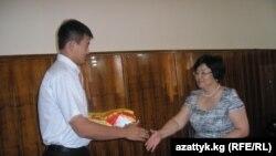 Жаш спортчулар Сингапурга жөнөөр алдында президент Роза Отунбаева Кыргызстандын туусун дзю-дочу Болотбек Токтогоновго тапшырууда, Бишкек, 9-август.