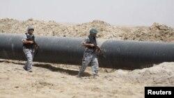 عناصر أمن عراقيون يحرسون أنبوباً لنقل النفط في الشعيبة