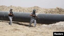 رجلا أمن يحرسان انبوبا للنفط في جنوب العراق (الارشيف)