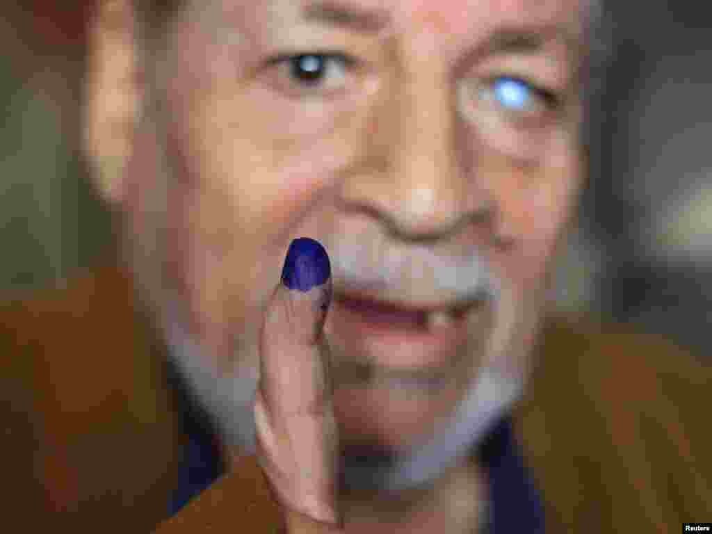 A man shows his finger after casting his vote at a polling station during Egyptian parliamentary elections in Cairo on November 28. (REUTERS/Ahmed Jadallah)
